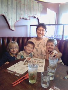 Helen Jones, our Warrior Wednesday spotlight, sits at a restaurant booth with her three children (two boys and a girl). They are all smiling. There's two menus and four glasses of water on the table in front of them.